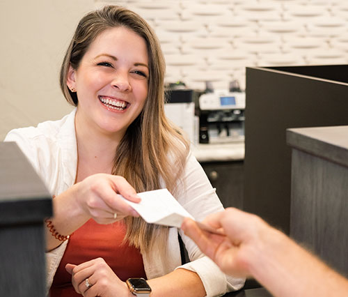 teller handing slip to customer for high-interest savings account