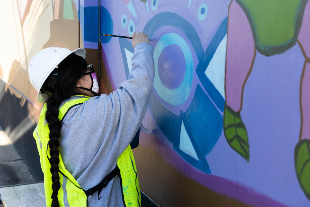 student working on the mural