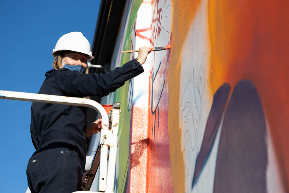 mentor artist working on the mural