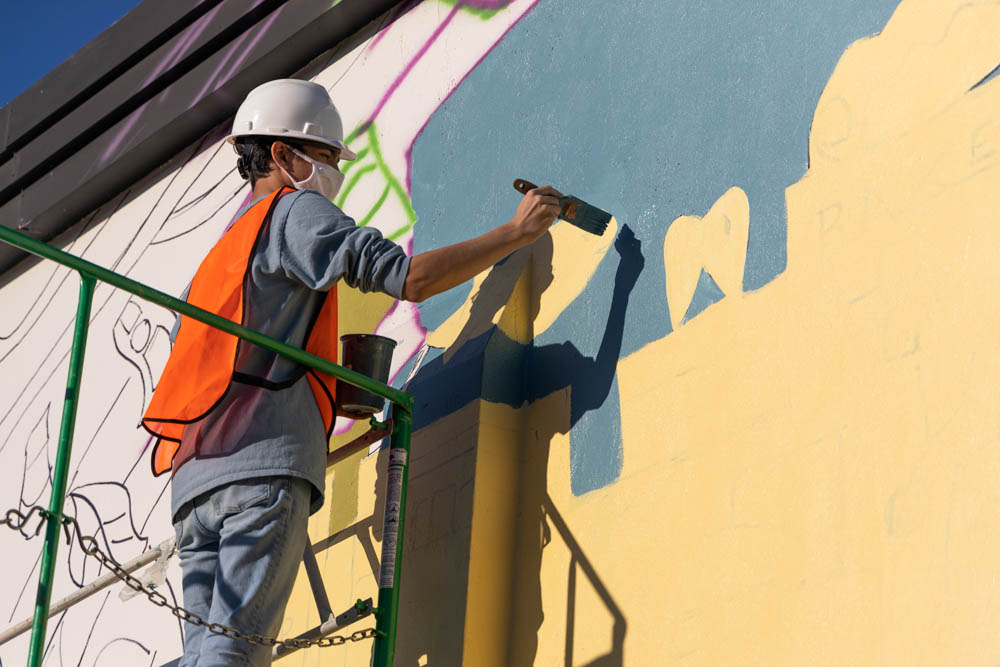 one of the student volunteers panting a portion of mural